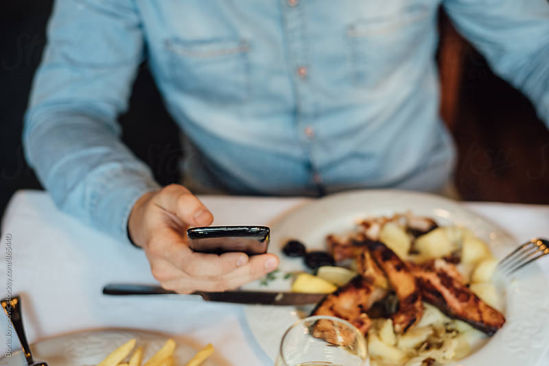 Man using a cellphone while having a lunch by Boris Jovanovic for Stocksy United