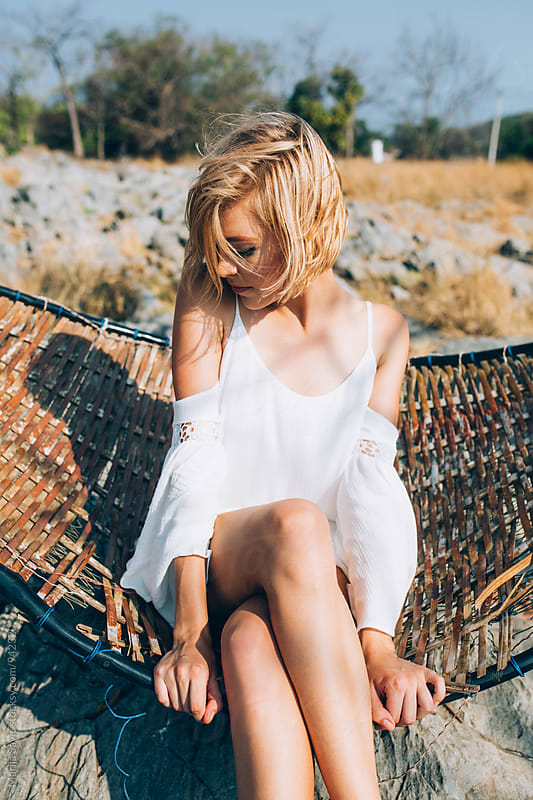 Close-up of blonde woman sitting on hammock by Marija Savic for Stocksy United