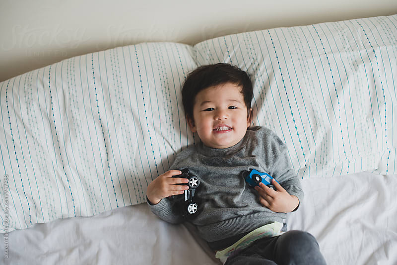 Toddler playing on bed by Lauren Naefe for Stocksy United