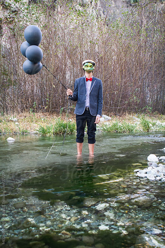 Man with Frog Mask and Balloons, Dreamy and Dark by MEGHAN PINSONNEAULT for Stocksy United