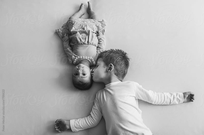 Brother and sister playing on bed by Peter Meciar for Stocksy United