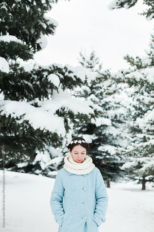 Little girl wearing a star wreath in the snowy woods by Jeremy and Alicia Brown Photography for Stocksy United