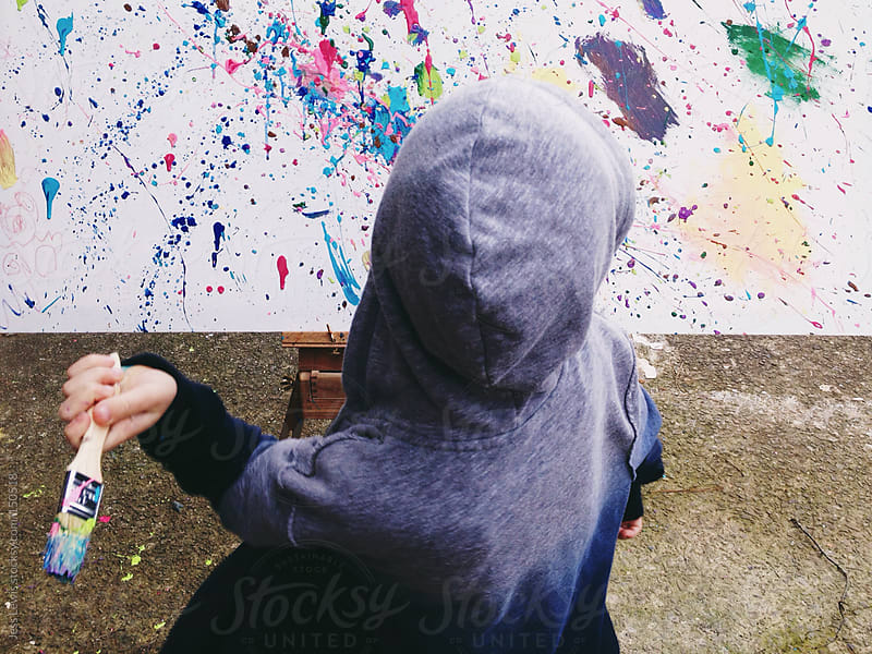 boy splattering paint onto canvas by Jess Lewis for Stocksy United