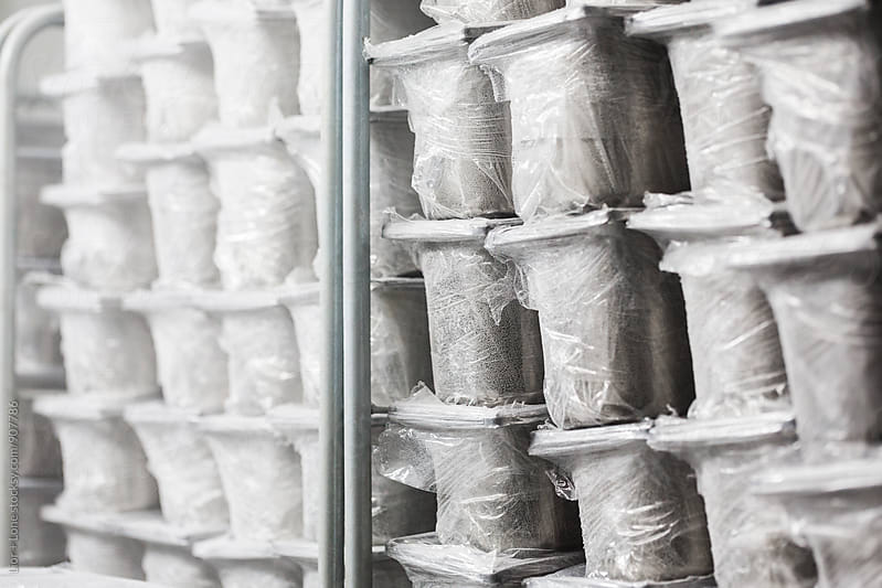 Various stainless steal ice cream containers in deep freeze by Lior + Lone for Stocksy United