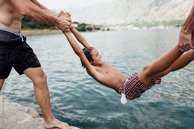 Friends trowing a young boy in to the water by Boris Jovanovic for Stocksy United