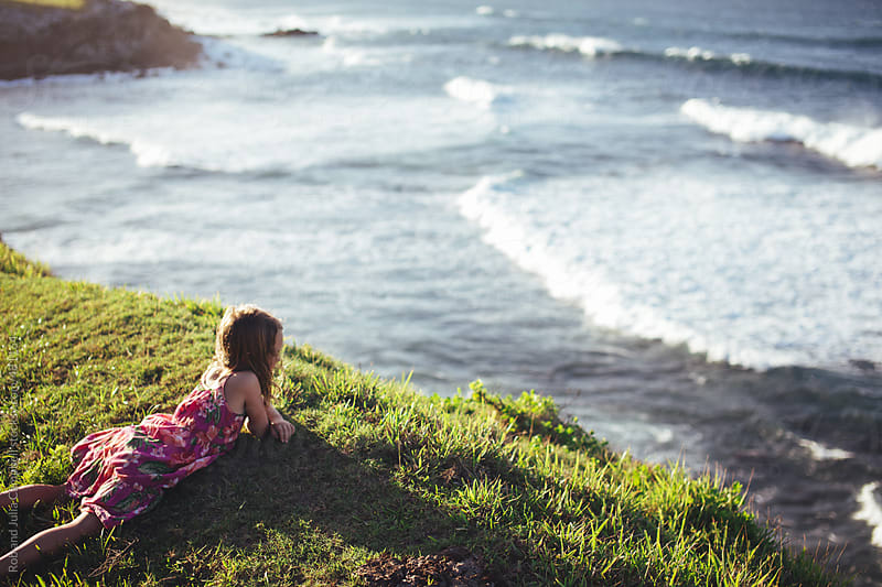Young girl in summer dress lying down on windy cliff at sunset looking at ocean by Rob and Julia Campbell for Stocksy United