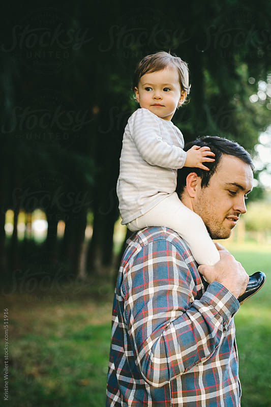 Father carrying his daughter on his shoulders by Kristine Weilert for Stocksy United