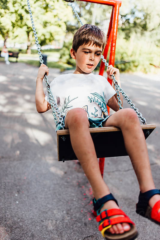 Boy swinging on the swing in the park by Boris Jovanovic for Stocksy United