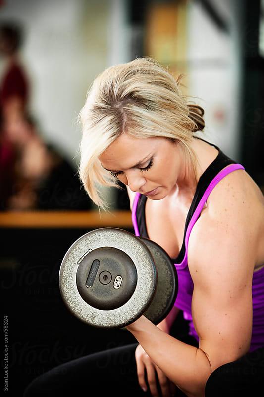 Gym: Woman Doing Bicep Curls by Sean Locke for Stocksy United
