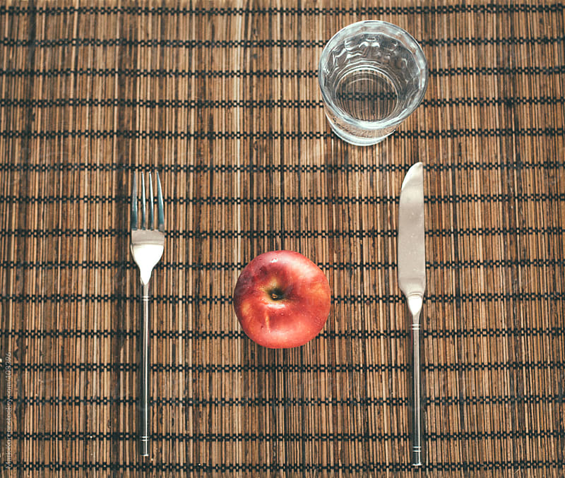 Apple among cutlery by Mark Korecz for Stocksy United