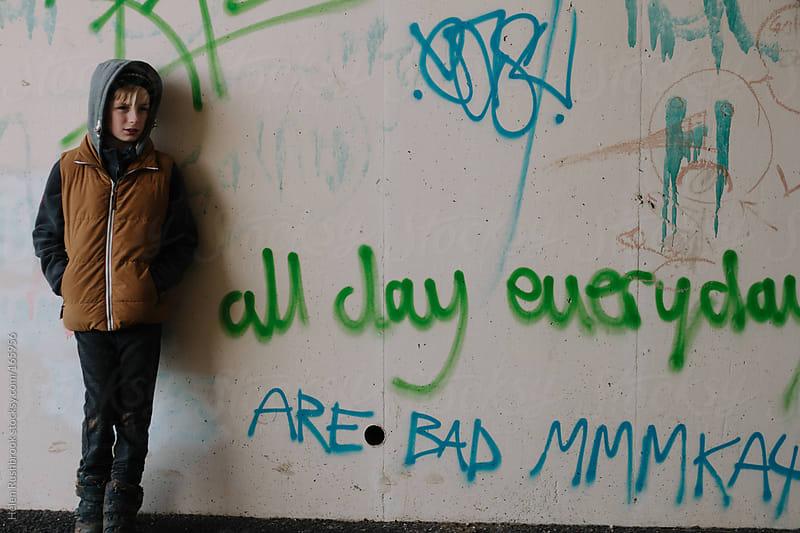 A boy alongside a heavily grafittied wall by Helen Rushbrook for Stocksy United