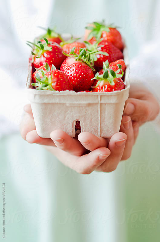 young woman holding strawberries by Canan Czemmel for Stocksy United