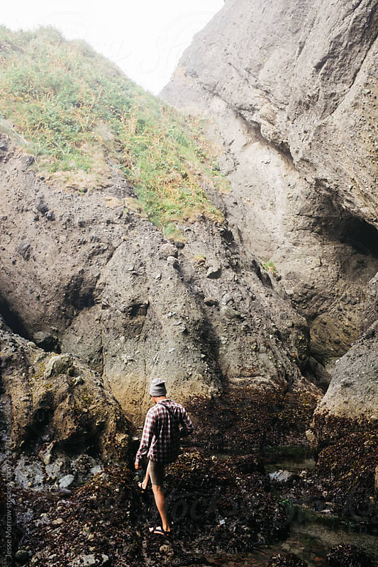 young male explores cracks in rocks and tidal pools by Jesse Morrow for Stocksy United