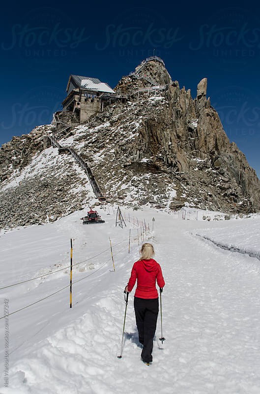 Young woman walking towards Grands Montets cable car station by Neil Warburton for Stocksy United