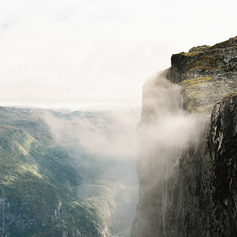 Low hanging clouds passing by a cliff in Norway by Atle Rønningen for Stocksy United