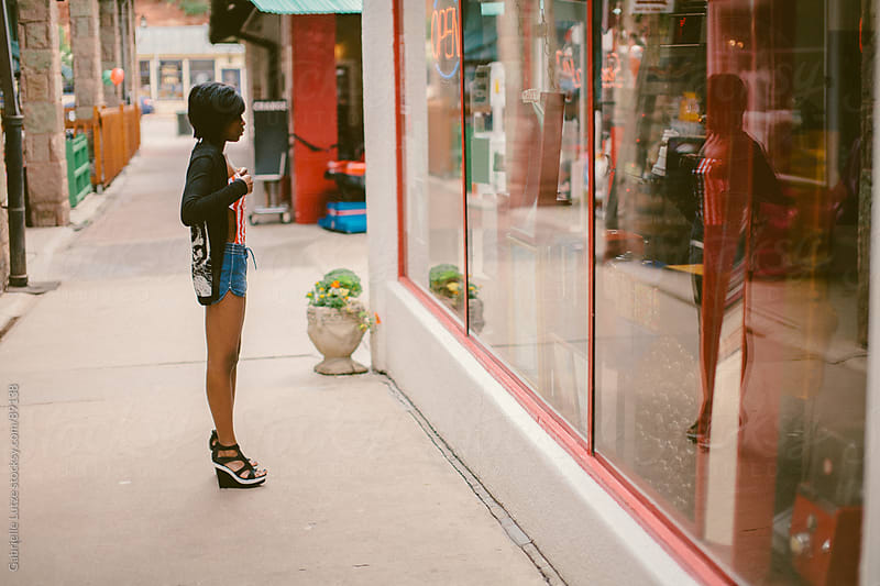 Black girl looking at her reflection at an arcade by Gabrielle Lutze for Stocksy United