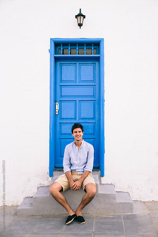 Smiling man sitting on steps in front of blue door by Alejandro Moreno de Carlos for Stocksy United