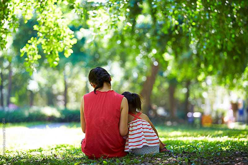 little girl and her mother sitting together outdoor in the sunny park by Bo Bo for Stocksy United