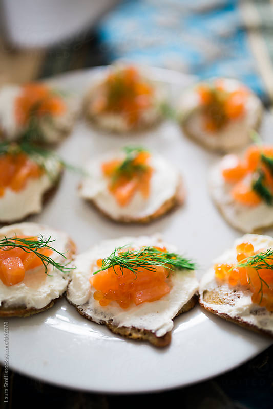 Close up of dish of blinis with sour cream, smoked salmon, caviar and fresh dill on plate by Laura Stolfi for Stocksy United