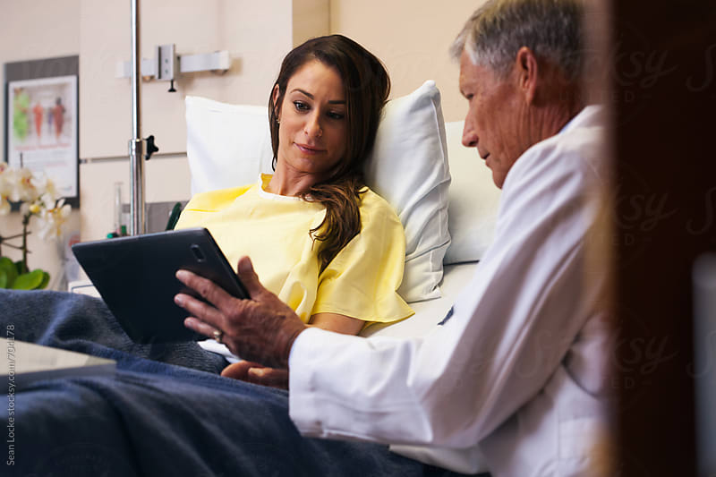 Hospital: Focus On Smiling Patient Looking At Tablet by Sean Locke for Stocksy United