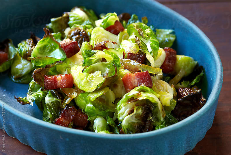 Blue side dish of roasted brussels sprouts and thick cut bacon by Sherry Heck for Stocksy United