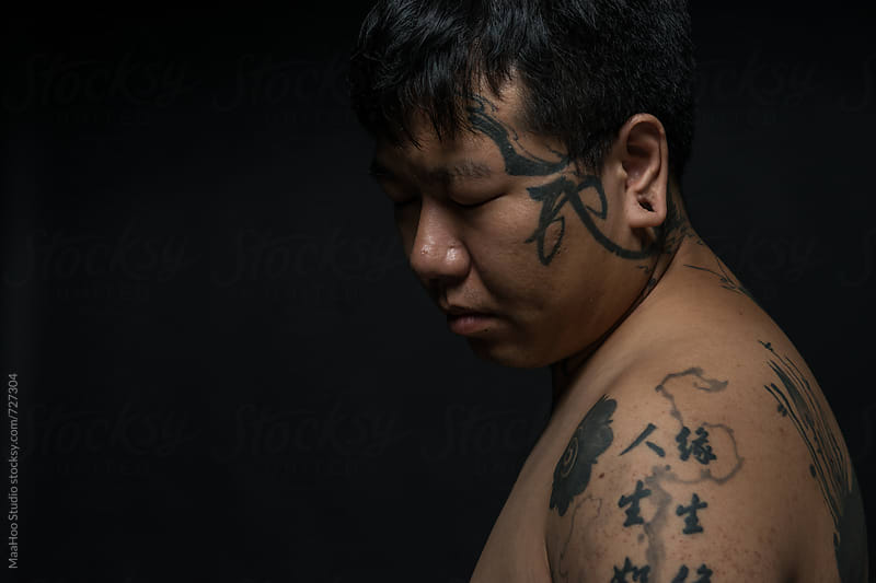 Portrait of young man with tattooed upper body by Maa Hoo for Stocksy United