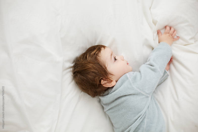 Toddler in a dreamy mood lying on the bed by Miquel Llonch for Stocksy United