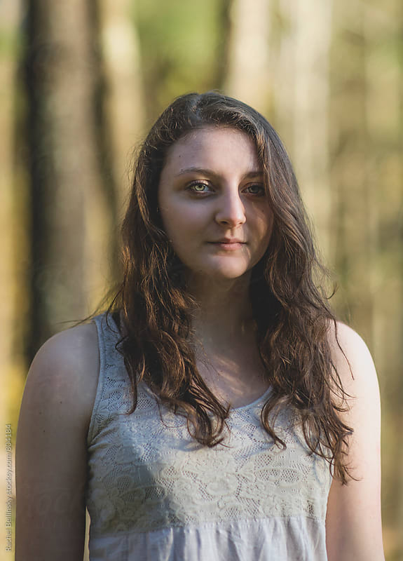 A young woman in the woods with sunlight on her face  by Rachel Bellinsky for Stocksy United