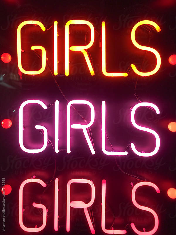 Neon signs lit at night, says girls girls girls by Leandro Crespi for Stocksy United