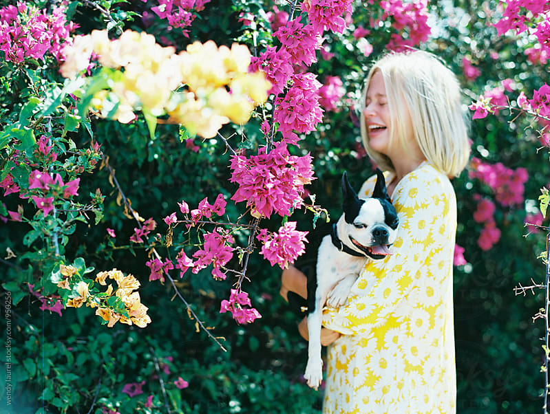 girl holding boston terrier in front of pink flowers by wendy laurel for Stocksy United