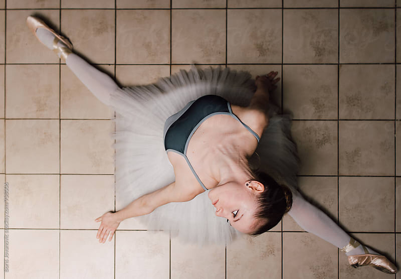 Ballerina doing splits on the floor by Boris Jovanovic for Stocksy United