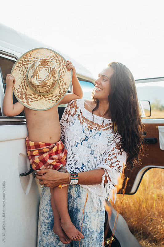 Young Pretty Hippie Mother Holding Cute Young Boy Hiding Behind Straw Hat by Julien L. Balmer for Stocksy United