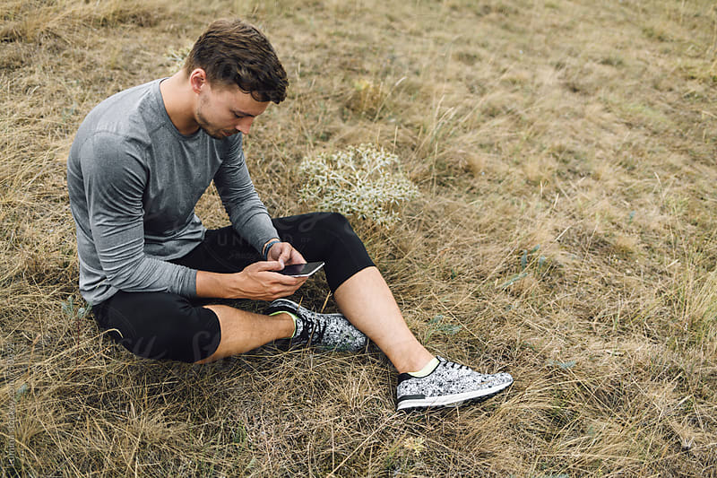 Man in Sportswear With a Mobile Phone Sitting on the Ground  by Lumina for Stocksy United