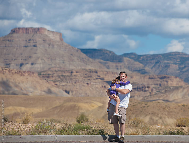 Western Road Trip: Father Holds Sleeping Daughter At Rest Stop V by Brian McEntire for Stocksy United