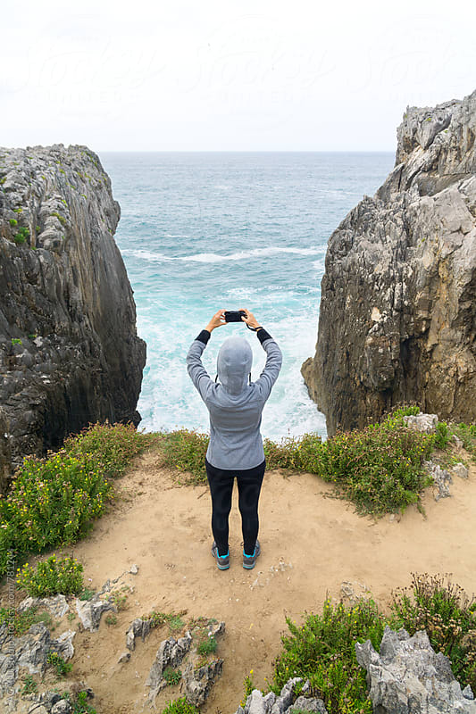 Woman taking a picture of the sea from a cliff by ACALU Studio for Stocksy United