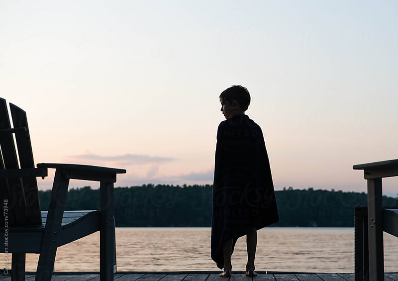 Boy wrapped up in towel stands on a dock on a summer evening by Cara Slifka for Stocksy United
