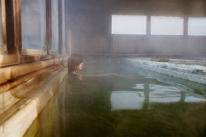 Woman relaxing in water at Japanese spa and hot springs by Trinette Reed for Stocksy United
