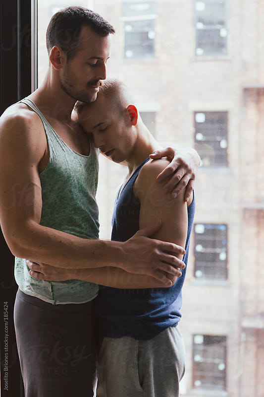 Gay Male Jock Couple Holding Each Other by Window by Joselito Briones for Stocksy United