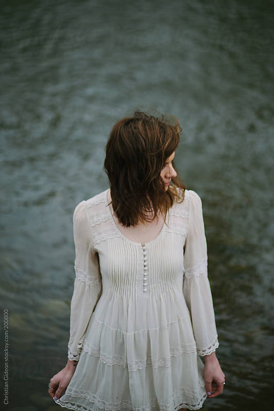 Girl next to river in white dress by Christian Gideon for Stocksy United