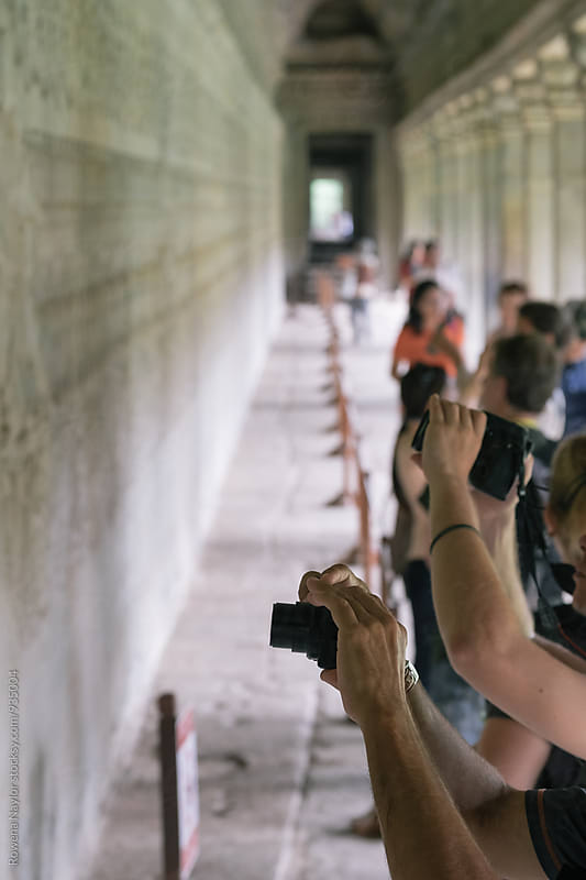 Tourists taking photos of ancient carved ruins at Angkor Wat, Cambodia by Rowena Naylor for Stocksy United