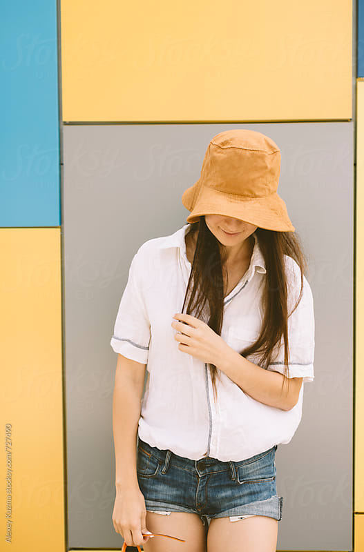 summer portrait of young woman with hat on the colorful background by Alexey Kuzma for Stocksy United