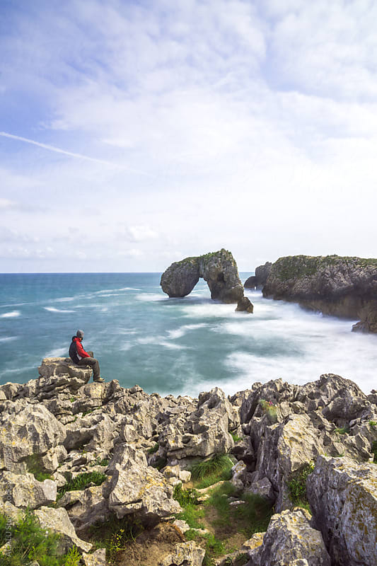 Man looking at natural arch on the sea by ACALU Studio for Stocksy United