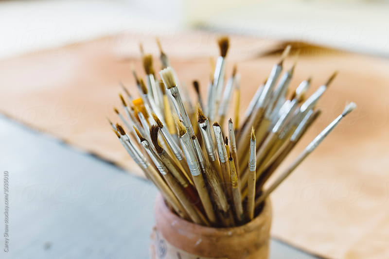 Paint brushes in arts studio by Carey Shaw for Stocksy United