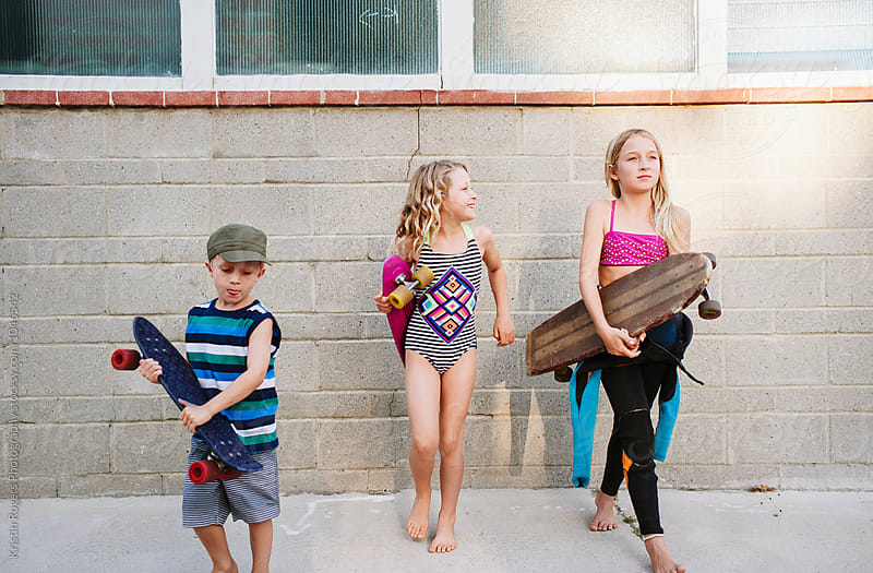 Group of  young kids with skateboards headed to beach by Kristin Rogers Photography for Stocksy United