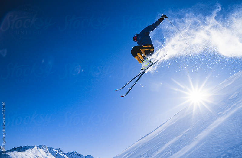 Male adult skier jumpin in powder snow in St Anton Austria by Soren Egeberg for Stocksy United