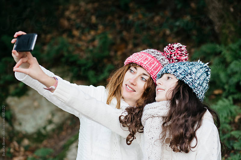 Mother and daughter taking a selfie of them selves by Beatrix Boros for Stocksy United