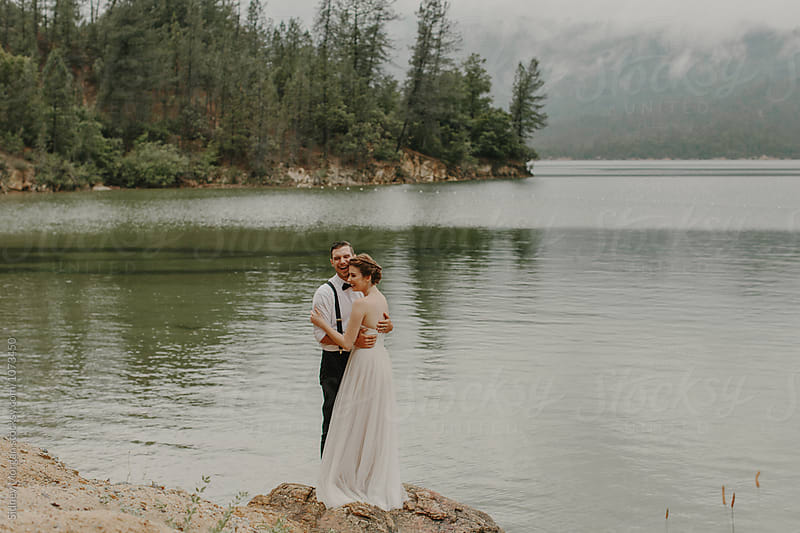 Bride and Groom by Lake by Sidney Morgan for Stocksy United