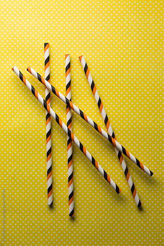 Straws and yellow polka dot background. by Robert Zaleski for Stocksy United