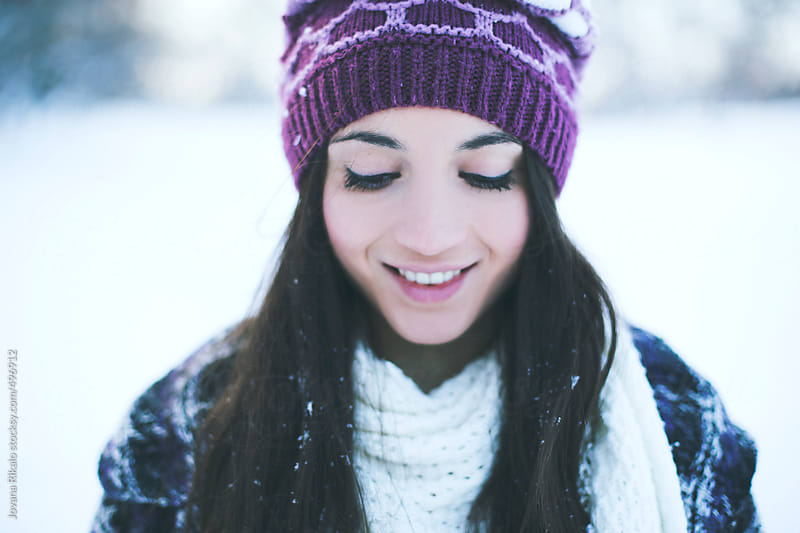 Portrait of a smiling young woman on a cold snowy day by Jovana Rikalo for Stocksy United