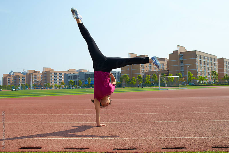 one young asian woman doing handstand outdoor by cuiyan Liu for Stocksy United
